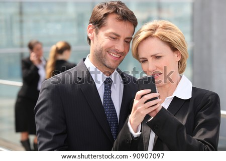 Business colleagues looking at phone - stock photo