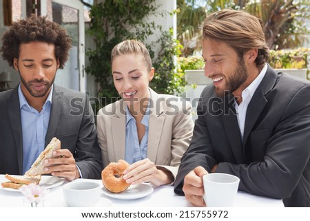 Business colleagues on their lunch outside at the coffee shop - stock photo