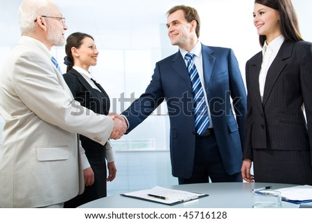 Business colleagues shaking hands - stock photo