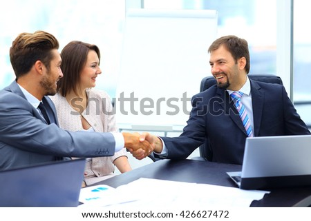 Business colleagues sitting at a table during a meeting with two - stock photo