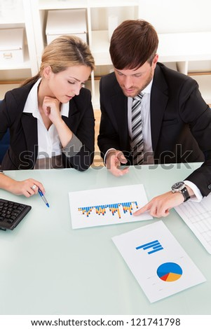 Business colleagues sitting together at a table in an office discussing and analyzing a bar graph