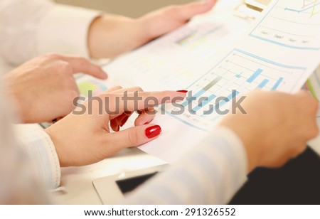 Business colleagues sitting together at table and viewing documents - stock photo