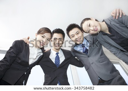 Business colleagues standing in huddle, arm around,low angle view - stock photo