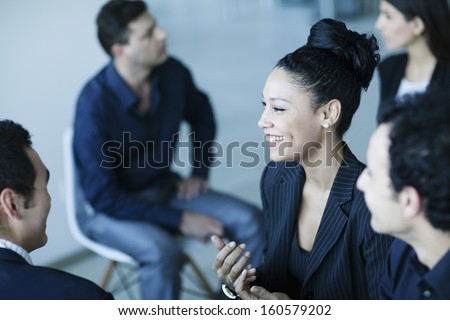 Business colleagues talking amongst themselves in office - stock photo