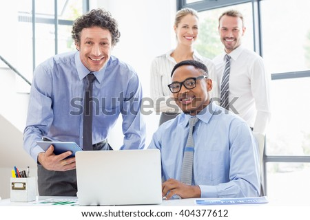 Business colleagues using laptop and digital tablet at desk - stock photo