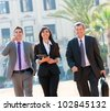 Business colleagues walking outdoors with digital tablet. - stock photo