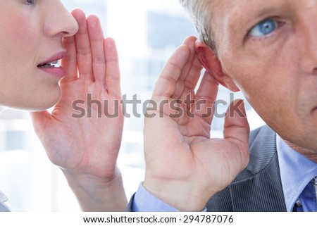 Business colleagues whispering to each other in the office - stock photo
