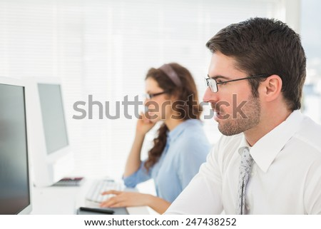 Business colleagues with glasses using computer in the office - stock photo
