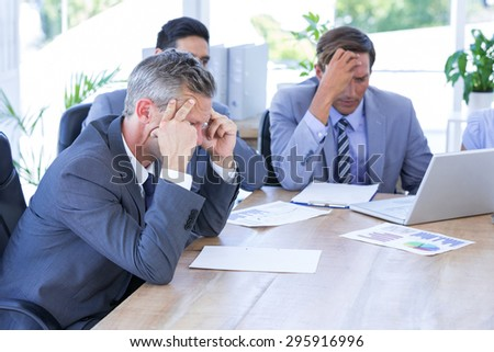 business colleagues with laptop and digital tablet in meeting at office desk - stock photo