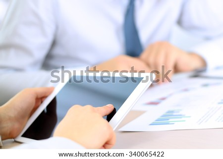 Business colleagues working and analyzing financial figures on a digital tablet - stock photo