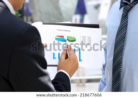 business colleagues working together and analyzing financial figures on a graphs - stock photo