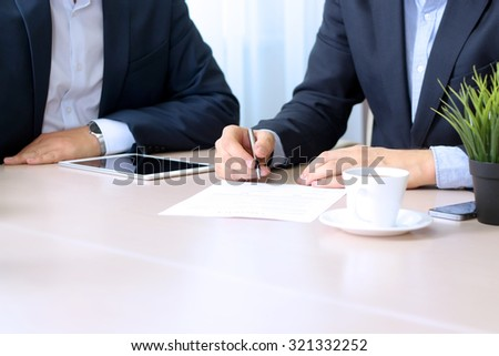business colleagues working together. Businessman is signing a contract - stock photo