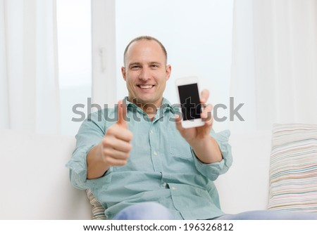 business, communication, home and modern technology concept - smiling man with smartphone at home showing thumbs up - stock photo