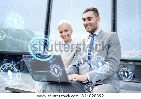 business, communication, technology and people concept - smiling businesspeople working with laptop computer and network projection on city street - stock photo