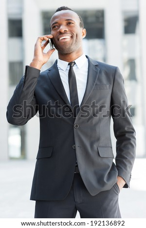 Business communications. Happy young African man in formal wear talking on the mobile phone and smiling while standing outdoors - stock photo