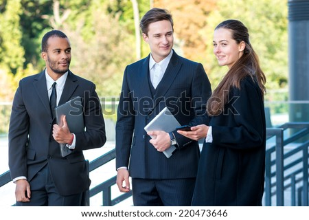 Business company. Three confident businessman holding a tablet and a laptop in the hands while standing on the street in formal wear looking on each other and smiling