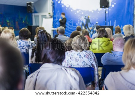 Business Concept and Ideas. Female Lecturer Speaking In front of the Large Group of People. Horizontal Image