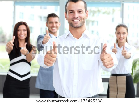 business concept - attractive businessman with team in office showing thumbs up  - stock photo