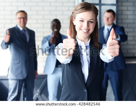 business concept - attractive businesswoman with team in office showing thumbs up