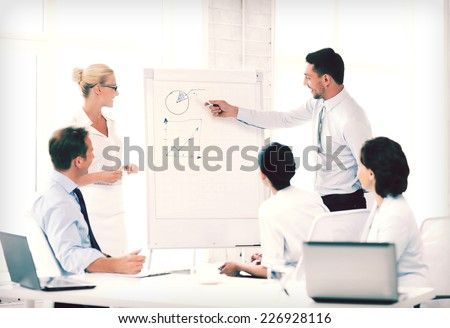 business concept - business team working with flipchart in office - stock photo