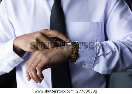 business concept,businessman correcting a tie on black background