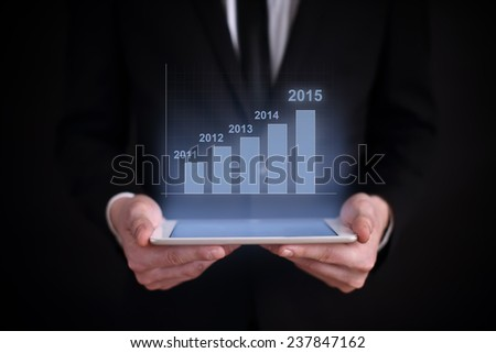 business concept. businessman holding a tablet with the projection of the financial growth per year graph above the screen. . 2015 . - stock photo