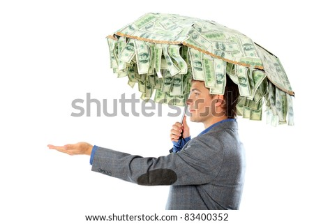 Business concept: businessman holding an umbrellar of money. Isolated over white. - stock photo