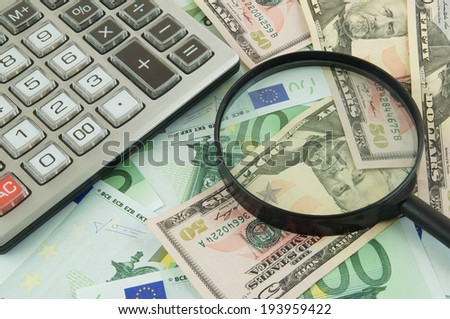 Business concept, calculator and magnifying glass on money background