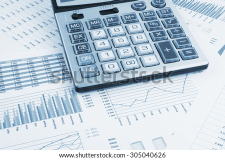 Business concept, calculator on financial charts and graphs