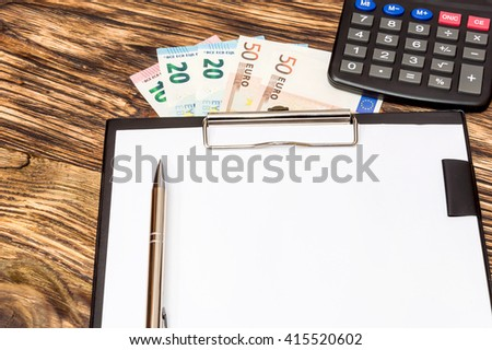 Business concept. Calculator, pen, money with clipboard on the table