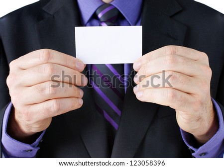 Business concept: caucasian hands of a businessman in dark suit with purple shirt and striped tie, holding a blank card, ready for your text.