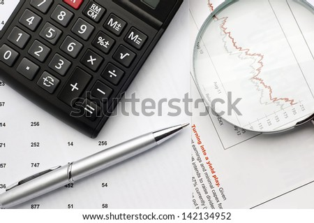 Business concept. Close up of Calculator, pen near magnifying glass and business paper
