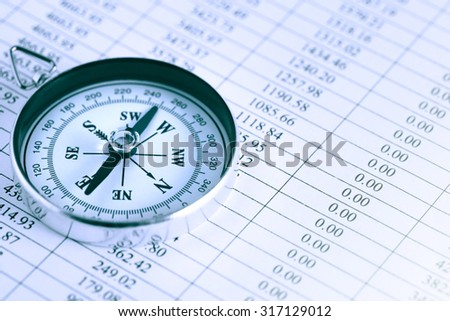 Business concept. Closeup of compass on paper list with digits - stock photo