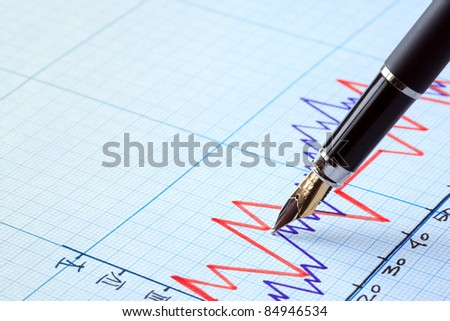Business concept. Closeup of fountain pen on graph paper with diagram