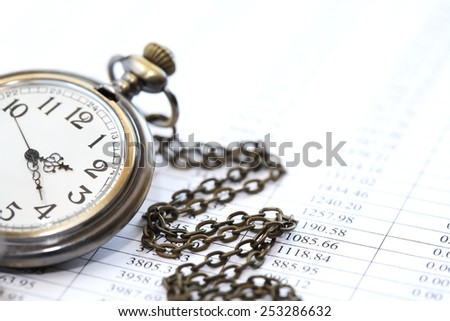 Business concept. Closeup of pocket watch on paper background with digits - stock photo