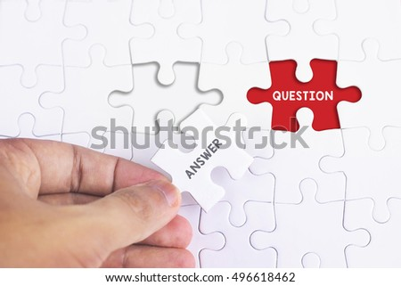 Business Concept - Female hand and missing puzzle with ANSWER and QUESTION WORD