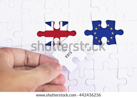 Business Concept - Female hand and missing puzzle with EUROPE AND BRITAIN FLAG.