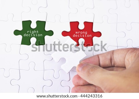 Business Concept - Female hand and missing puzzle with Right Decision - Wrong Decision word - stock photo