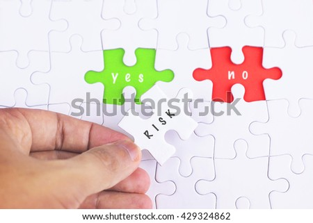 Business Concept - Female hand and missing puzzle with RISK, YES and no WORD