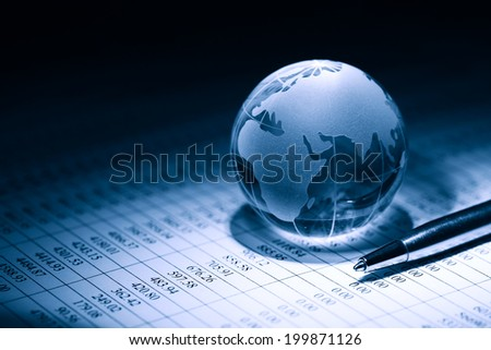 Business concept. Glass globe near pen on background with table of numbers - stock photo