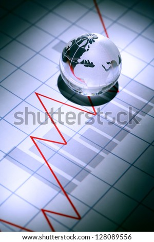 Business concept. Glass globe on paper background with chart - stock photo