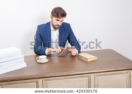 Business concept - handsome man with beard and brown hair and blue suit and tablet pc computer and some books holding tablet, working and sitting in the office.  Isolated on white background.   - stock photo