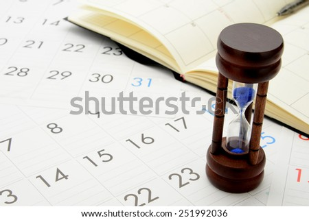 Business concept, hourglass and personal organizer on calender - stock photo