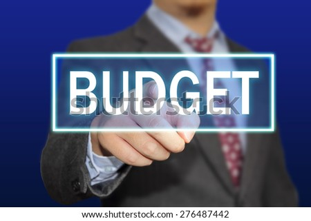 Business concept image of a businessman clicking Budget button on virtual screen over blue background