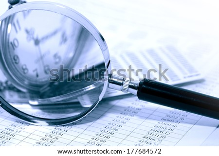 Business concept. Magnifying glass near pocket watch on paper background with digits - stock photo