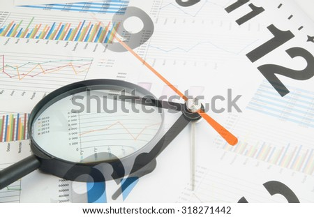 Business concept, magnifying glass on financial charts and graphs, collage with clock