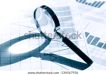 Business concept. Magnifying glass on paper background with chart - stock photo