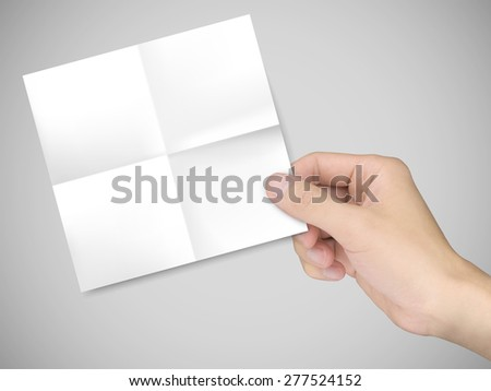 business concept: man's hand holding a note paper over grey background - stock photo