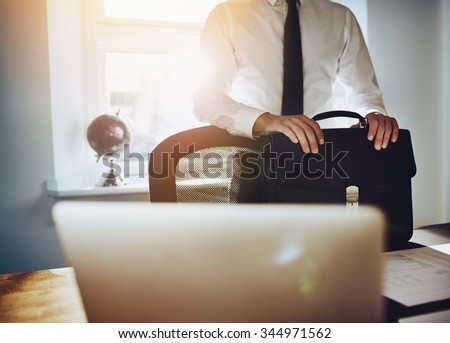 Business concept, man standing at desk with briefcase and laptop wearing a classic business outfit - stock photo