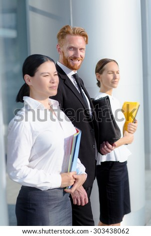Business concept of successful people. Three collegues waiting for their important partners outside near office building.